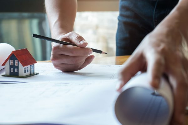 Architect has a pen and house plan in hand.house plans and home model on desk.